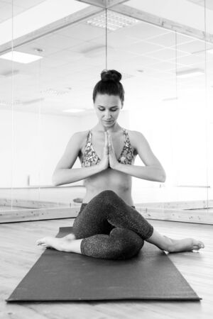 Fit sporty active girl in fashion sportswear doing yoga fitness exercise in yoga studio. Active urban lifestyle. Black and white photo.