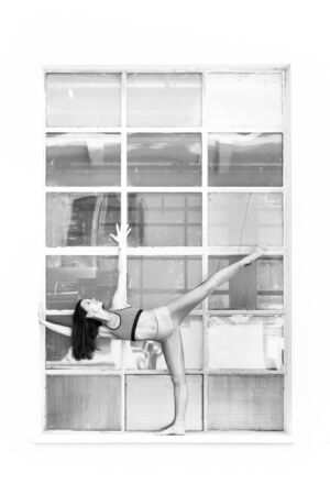Fit sporty active girl in fashion sportswear doing yoga fitness exercise in front of big industrial window frame. colorful reflections in window glass. Urban style yoga. Black and white. 写真素材