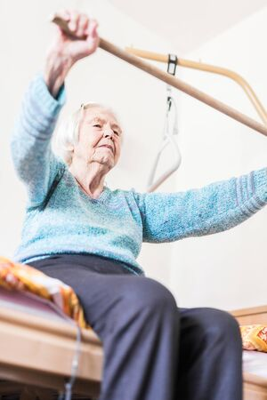 Elderly 96 years old woman exercising with a stick sitting on her bad. Geriatric health care home assisted support for older people concept. Care for the elderly. Archivio Fotografico
