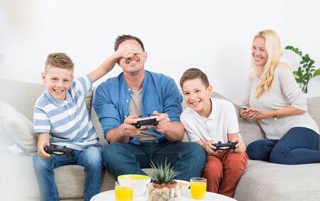 Heureuse jeune famille jouant à la console de jeux vidéo à la télévision. Passer du temps de loisirs de qualité avec les enfants et le concept de famille. Les consoles de jeu sont génériques et sans marque.