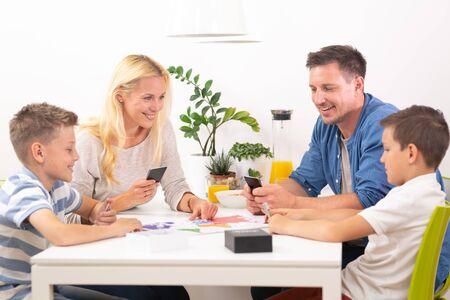 Gelukkig jong gezin speelkaartspel aan eettafel in lichte moderne woning. Kwaliteitsvrije tijd doorbrengen met kinderen en familieconcept. Kaarten zijn generiek en merkloos. Stockfoto