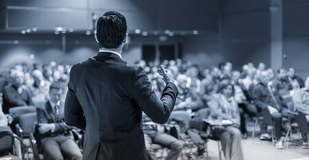 Speaker giving a talk on corporate business conference. Unrecognizable people in audience at conference hall. Business and Entrepreneurship event. Black and white image. 版權商用圖片