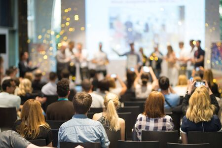 Young business team receiving award prize at best business project competition event. Business and entrepreneurship award ceremony theme. Focus on unrecognizable people in audience. Standard-Bild