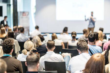 Symposium sur les affaires et l'entrepreneuriat. Président donnant une conférence lors d'une réunion d'affaires. Public dans la salle de conférence. Vue arrière d'un participant non reconnu dans l'audience.