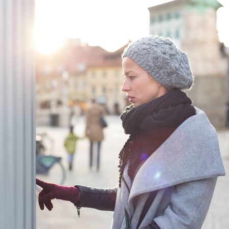 Casual woman buying public transport tickets on city urban vedning machine on cold winter day in Ljubljana, Slovenia.