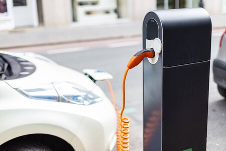 Power supply for electric car charging. Electric car charging station. Close up of the power supply plugged into an electric car being charged. 版權商用圖片