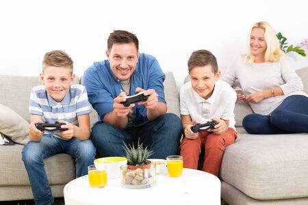 Happy young family playing videogame console on TV. Spending quality leisure time with children and family concept. Gaming consoles are generic and debranded. 版權商用圖片