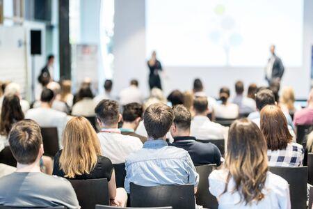 Simposio su imprese e imprenditoria. Relatore durante un incontro di lavoro. Pubblico nella sala conferenze. Retrovisione del partecipante non riconosciuto nel pubblico.