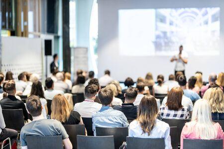 Publiek in de conferentiezaal. Mannelijke spreker die een lezing geeft in de conferentiezaal op een zakelijk evenement. Business en ondernemerschap concept. Focus op onherkenbare mensen in het publiek. Stockfoto