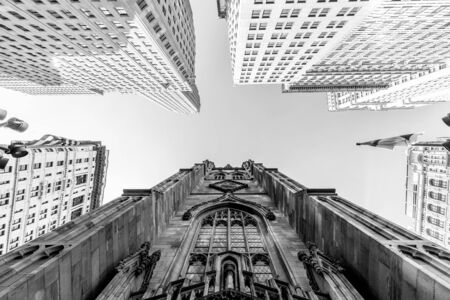 Wide angle upward view of Trinity Church at Broadway and Wall Street with surrounding skyscrapers, Lower Manhattan, New York City, USA. Black and white image. Imagens