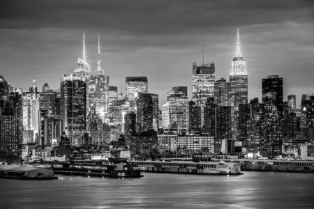 West New York City midtown Manhattan skyline panorama view from Boulevard East Old Glory Park over Hudson River at night. Black and white image.