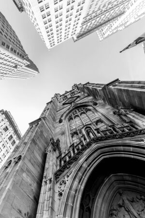 Wide angle upward view of Trinity Church at Broadway and Wall Street with surrounding skyscrapers, Lower Manhattan, New York City, USA. Black and white image. Stock fotó
