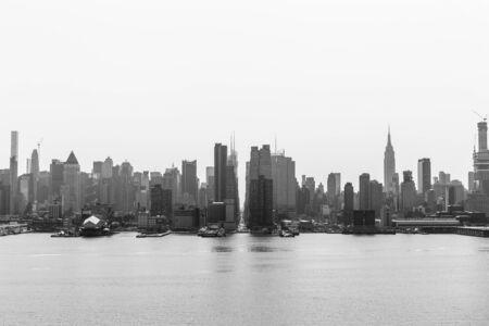 New York City midtown Manhattan skyline panorama view from Boulevard East Old Glory Park over Hudson River on a misty morning. Black and white image.