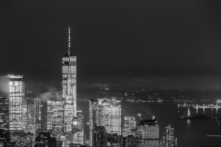 New York City skyline with lower Manhattan skyscrapers in storm at night. Black and white image. Imagens