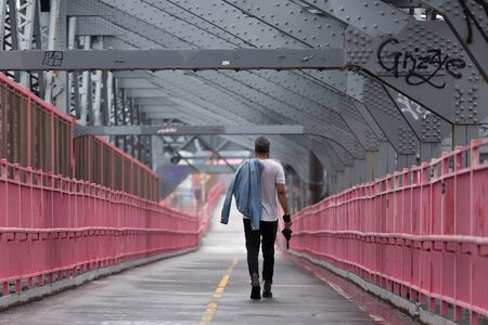 Rear view of unrecognizable stylish young man carrying jeans jacket over his shoulder walking on Williamsburg Bridge, Brooklyn, New York City, USA.