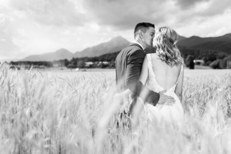 Bride and groom kissing and hugging tenderly in wheat field somewhere in Slovenian countryside. Caucasian happy romantic young couple celebrating their marriage. Black and white photo.