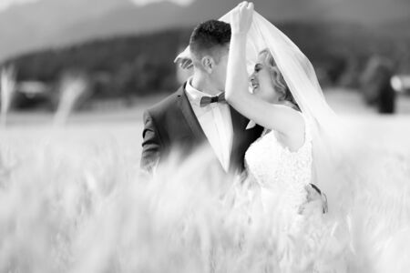 Groom hugs bride tenderly while wind blows her veil in wheat field somewhere in Slovenian countryside. Caucasian happy romantic young couple celebrating their marriage. Black and white photo.