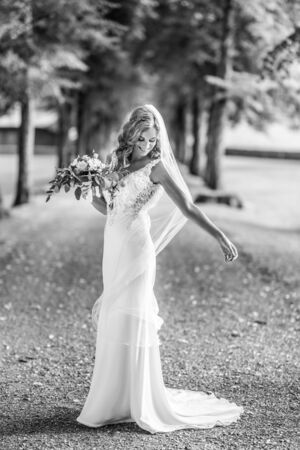 Full length portrait of beautiful sensual young blond bride in long white wedding dress and veil, holding bouquet outdoors in natural background. Black and white photo.