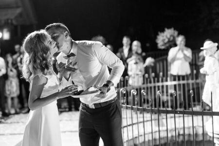 Sposa e sposo felici che si disordinano mangiando un pezzo di torta nuziale con le mani dopo averlo tagliato. Consuetudine tradizionale della celebrazione del matrimonio. Immagine in bianco e nero. Archivio Fotografico