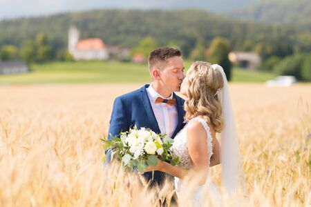 Bride and groom kissing and hugging tenderly in wheat field somewhere in countryside in Slovenian . Caucasian happy romantic young couple celebrating their marriage. Stock Photo
