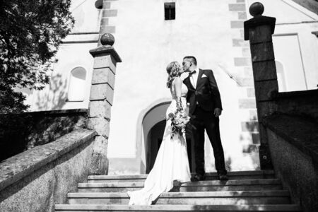 The Kiss. Bride and groom kisses tenderly on a staircase in front of a small local church. Stylish wedding couple kissing. Black and white photo.