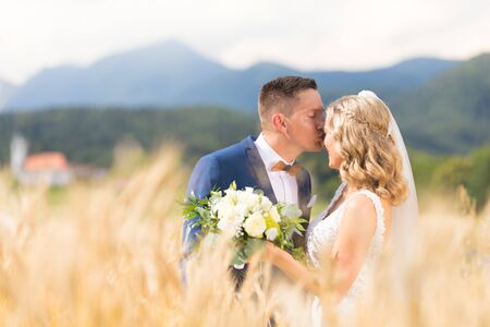 Groom hugging bride tenderly and kisses her on forehead in wheat field somewhere in Slovenian countryside. Caucasian happy romantic young couple celebrating their marriage.