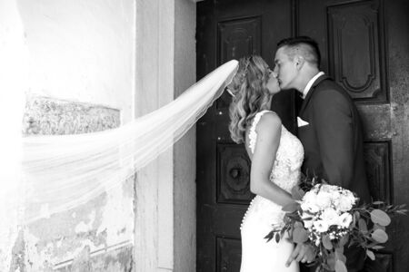 The Kiss. Bride and groom kisses tenderly in front of church portal. Close up portrait of sexy stylish wedding couple kissing. Black and white photo.