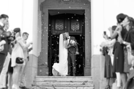 Newlyweds kissing while exiting the church after wedding ceremony, family and friends celebrating their love with the shower of soap bubbles, custom undermining traditional rice bath. Black and white. Stock Photo