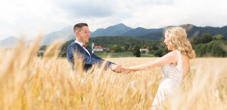 Groom and bride holding hands in wheat field somewhere in Slovenian countryside. Caucasian happy romantic young couple celebrating their marriage.