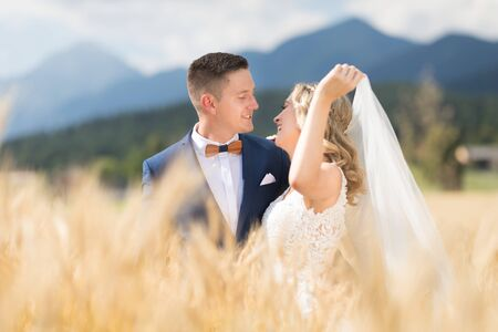Groom hugs bride tenderly while wind blows her veil in wheat field somewhere in Slovenian countryside. Caucasian happy romantic young couple celebrating their marriage.