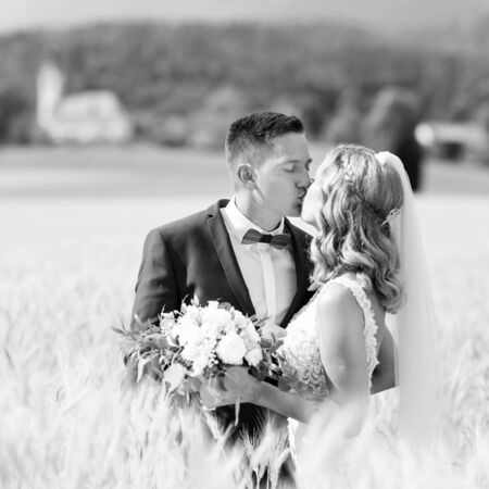 Bride and groom kissing and hugging tenderly in wheat field somewhere in countryside in Slovenian . Caucasian happy romantic young couple celebrating their marriage. Black and white photo.
