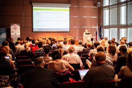 Zakelijk en ondernemerschap symposium. Spreker houdt een lezing op zakelijke bijeenkomst. Publiek in conferentiezaal. Achteraanzicht van niet-herkende deelnemer in publiek.