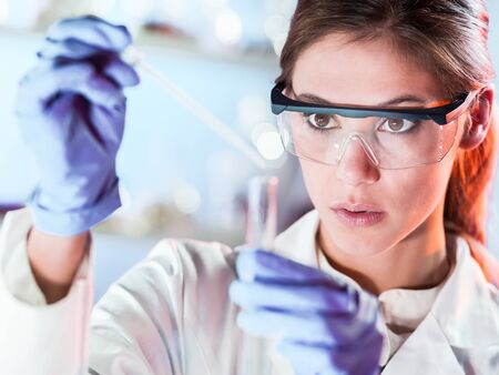 Life scientists researching in laboratory. Focused female life science professional pipetting solution into the glass cuvette. Lens focus on researchers eyes. Healthcare and biotechnology concept. 写真素材
