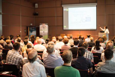 Zakelijk en ondernemerschap symposium. Spreker houdt een lezing op zakelijke bijeenkomst. Publiek in conferentiezaal. Achteraanzicht van niet-herkende deelnemer in publiek. Stockfoto