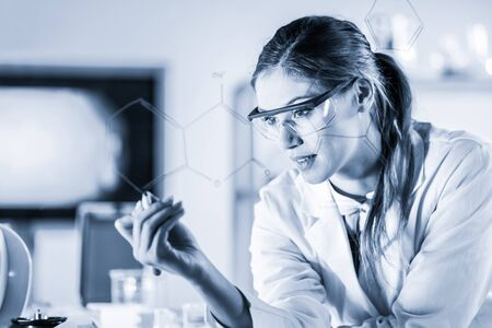 Portrait of a confident female health care expert in life science laboratory writing structural chemical formula on a glass board. Healthcare and modern life science concept. Blue toned image.