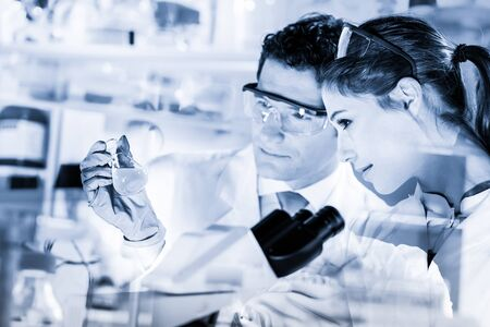 Chemical laboratory. Attractive young PhD student and her post doctoral supervisor scientist observing the blue indicator color shift after the solution destillation.