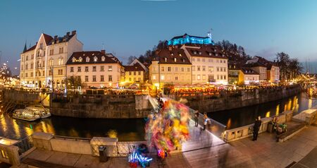 View of lively river Ljubljanica bank in old city center decorated with Christmas lights at dusk. Old medieval Ljubljana cstle on the hill obove the city. Ljubljana, Slovenia, Europe. 스톡 콘텐츠