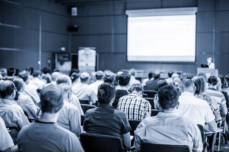 Speaker giving talk at business event. Audience at the conference hall. Business and Entrepreneurship concept. Focus on unrecognizable people in audience. Blue toned grayscale image. Zdjęcie Seryjne