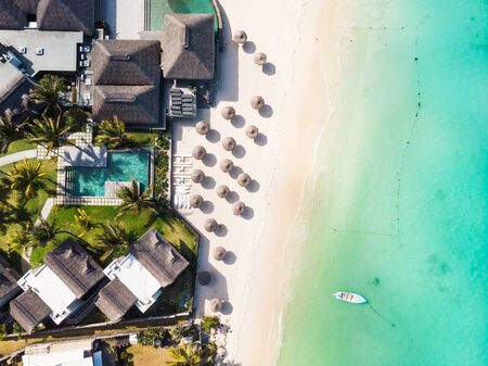 Aerial view of beautiful tropical beach front hotel resort with swimming pool, palm leaves umbrellas and turquoise sea. Paradise destination for vacations in Mauritius.