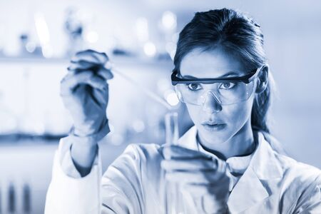 Life scientists researching in laboratory. Focused female life science professional pipetting solution into the glass cuvette. Healthcare and biotechnology concept. Blue toned image.