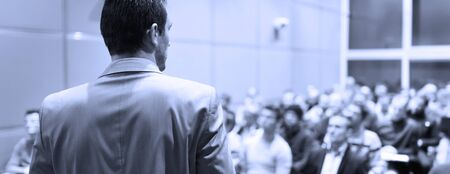 Speaker at Business Conference with Public Presentations. Audience at the conference hall. Business and Entrepreneurship concept. Background blur. Shallow depth of field. Blue toned.