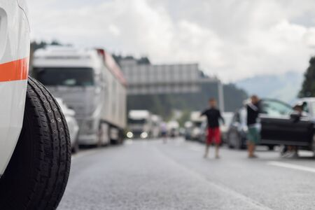 Typical scene on European highways during summer holiadays rush hour. A traffic jam with rows of cars tue to highway car accident. Empty emergency lane. Shallow depth of field.