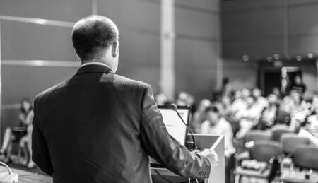 Speaker giving a talk on corporate business conference. Unrecognizable people in audience at conference hall. Business and Entrepreneurship event. Black and white image. Zdjęcie Seryjne