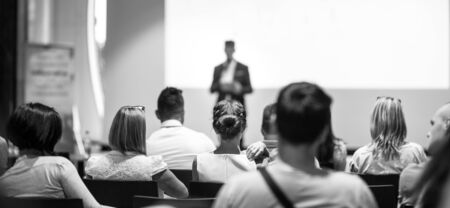 Speaker giving talk at business event. Audience at the conference hall. Business and Entrepreneurship concept. Focus on unrecognizable people in audience. Black and white photo.