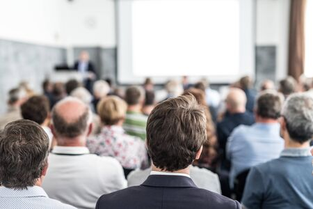 Speaker giving a talk in conference hall at business event. Audience at the conference hall. Business and Entrepreneurship concept. Focus on unrecognizable people in audience. Standard-Bild