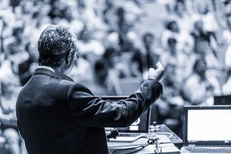 Speaker giving a talk on corporate business conference. Unrecognizable people in audience at conference hall. Business and Entrepreneurship event. Black and white, blue toned image.