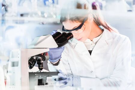 Life scientists researching in laboratory. Focused female young scientist microscoping in scientific working environment. Healthcare science and biotechnology.