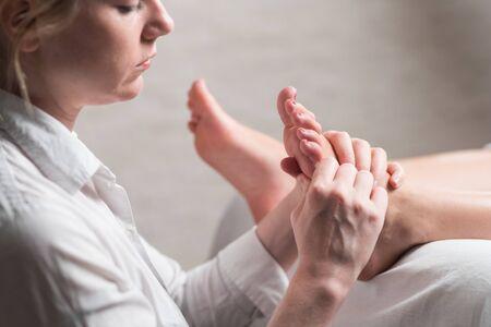 Massaggiatore femminile professionista che dà massaggio di riflessologia al piede della donna. Archivio Fotografico
