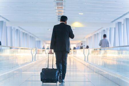 Vista posteriore di un irriconoscibile uomo d'affari vestito formalmente che cammina e spinge una valigia trolley nella hall, parlando al telefono cellulare. Concetto di viaggio d'affari.