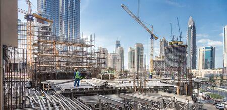 Obreros que trabajan en obras de construcción modernas en Dubai. Concepto de desarrollo urbano rápido.